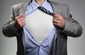 Businessman in classic superman pose tearing his shirt open to r